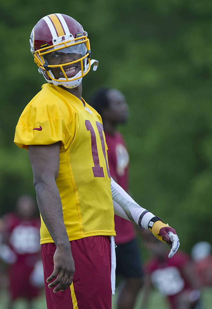 Newly drafted quarterback Robert Griffin III, aka RG3, smiles during Washington Redskins rookie minicamp at Redskins Park in Ashburn, Va. on Sunday, May 6, 2012. This was the first time first-round draft pick RG3 suited up in a Redskins jersey. (Barbara L. Salisbury/The Washington Times)