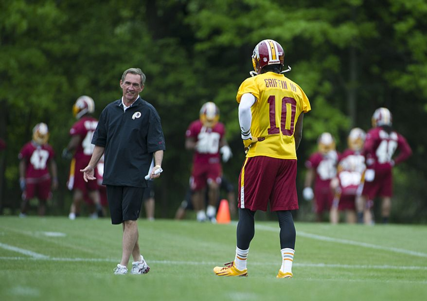 Washington Redskins Coach Mike Shanahan, left, talks with newly drafted quarterback Robert Griffin III. (Barbara L. Salisbury/The Washington Times)