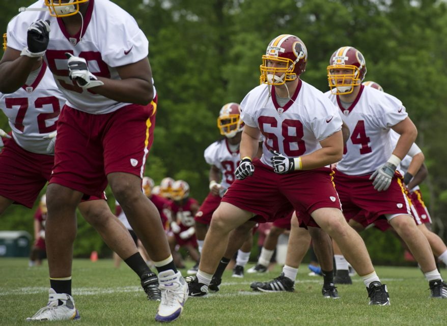 Tom Compton, center, # 68, an offensive tackle drafted from South Dakota, goes through stretching exercises at Redskins Park. (Barbara L. Salisbury/The Washington Times)