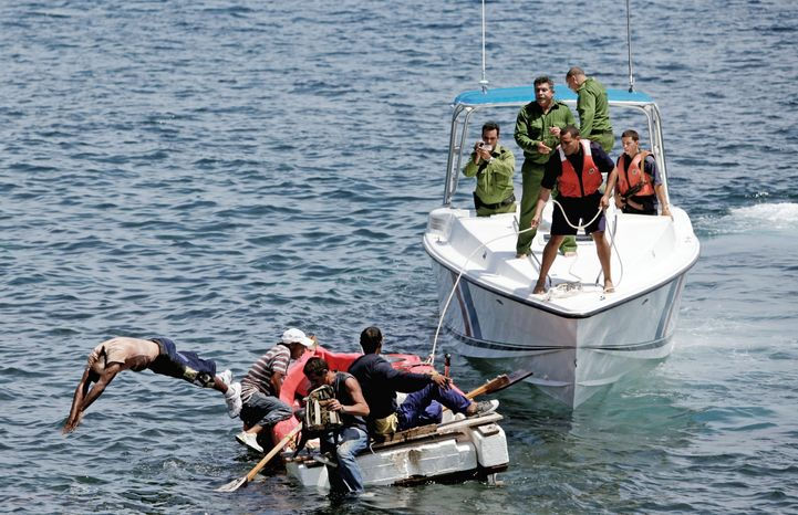 In this June 4, 2009 file photo, Cuban coast guards, right, stop men from trying to migrate illegally to the U.S. on a foam raft near Havana's Malecon. Cuba's government appears on the verge of a momentous decision that could end a half-century of travel restrictions that make it difficult to leave the Communist-run island, even for vacation. (AP Photo/Javier Galeano, File)