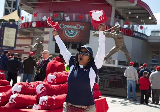 Diane Brantley hands out hats before the Nationals hosted the Cincinnati Reds in their home opener April 12. Washington posted an attendance of 106,931 for a three-game series with Philadelphia this past weekend. (Associated Press)