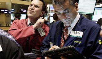 Traders Michael Zicchinolfi (left) and Vincent Quinones keep an eye on prices Monday on the floor of the New York Stock Exchange. U.S. stocks were under pressure after angry voters in Greece and France rejected painful budget cuts demanded by international lenders. But investors did not panic about the election news. (Associated Press)