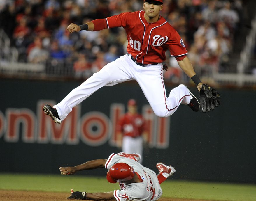 Washington Nationals shortstop Ian Desmond leaps over sliding Philadelphia Phillies base runner Juan Pierre at second base as he watches the completion of a double play on Shane Victorio's infield grounder during the fifth inning of a Major League Baseball game at Nationals Park in Washington on Sunday, May 6, 2012. The Phillies defeated the Nationals 9-3. (AP Photo/Richard Lipski)