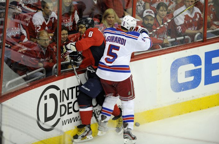 New York Rangers defenseman Dan Girardi fights for the puck against Washington Capitals left wing Alex Ovechkin, during the first period of Game 4 of an NHL Stanley Cup second-round playoff series, Saturday, May 5, 2012, in Washington. (AP Photo/Nick Wass)