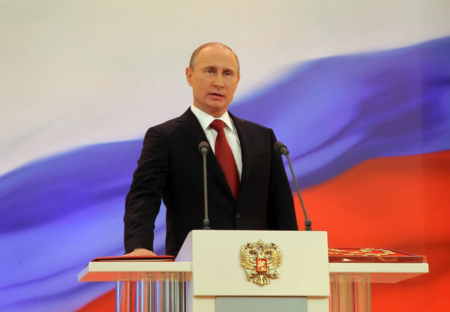 Vladimir Putin speaks with his hand on the Russian Constitution during his inauguration ceremony as the country's president in Moscow on Monday, May 7, 2012. (AP Photo/RIA Novosti Kremlin, Vladimir Rodionov, Presidential Press Service)
