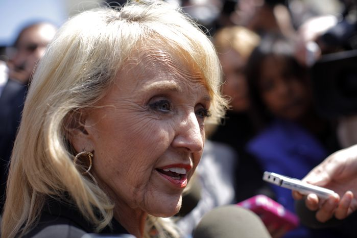 """Arizona Gov. Jan Brewer speaks to reporters outside the Supreme Court in Washington, Wednesday, April 25, 2012, after the court's hearing on Arizona's """"show me your pap"""
