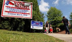 Signs backing and against the Constitutional Marriage Amendment line a sidewalk outside a polling site at Leesville Road Middle School in Raleigh, N.C., on Tuesday. A constitutional amendment to ban gay marriage was driving turnout for the state's primary. (Associated Press)
