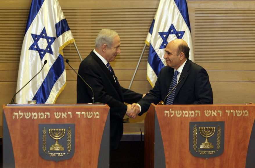 Israeli Prime Minister Benjamin Netanyahu (left) and Kadima party leader Shaul Mofaz shake hands before holding a joint press conference in Jerusalem on Tuesday, May 8, 2012, to announce Israel's new coalition government. (AP Photo/Sebastian Scheiner)