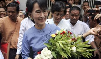 Myanmar opposition leader Aung San Suu Kyi (center) is greeted by supporters as she arrives for the ceremonial opening of a branch office of her National League for Democracy party on Tuesday, May 8, 2012, in Yangon, Myanmar. (AP Photo/Khin Maung Win)