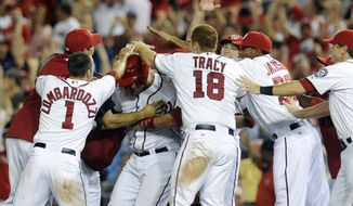 Washington Nationals' Wilson Ramos, center, is mobbed by teammates after hitting the game-winning RBI in the 11th inning to defeat the Philadelphia Phillies 4-3 at Nationals Park on Friday, May 4, 2012, in Washington. (AP Photo/Richard Lipski)