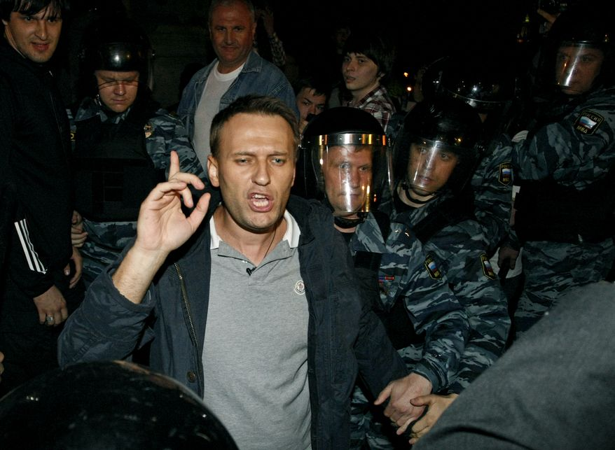 Russian riot police detain Alexei Navalny (center), a prominent anti-corruption whistle-blower and blogger, as he speaks to protesters gathered near the presidential administration offices in downtown Moscow early on Tuesday, May 8, 2012, a day after Vladimir Putin's inauguration as president. (AP Photo/Alexander Zemlianichenko Jr.)