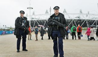 Police officers are ready outside the Olympic Stadium in London. They are part of the United Kingdom's largest ever peacetime security operation. (Associated Press)