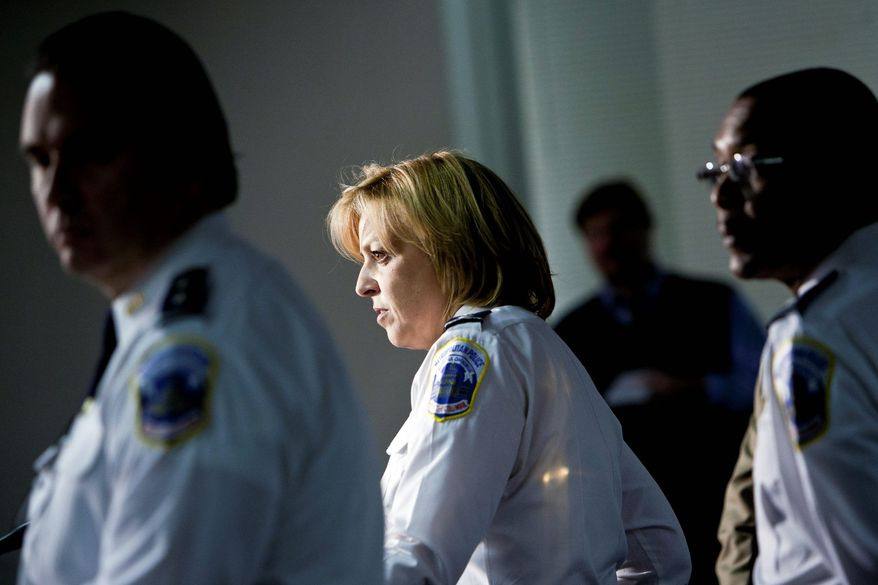 MPD Chief Cathy L. Lanier, center, with Assistant Chief Peter Newsham, left, and Commander Melvin Scott, right, speaks about an undercover operation that resulted in the arrest of 70 suspects and confiscation of firearms and narcotics with a value of more than $7.1 million at Metropolitan Police Department headquarters in Washington, D.C. on Dec. 19, 2011. (T.J. Kirkpatrick/ The Washington Times)