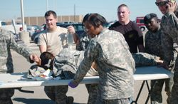 First responders transport a wounded soldier an ambulance at Fort Hood, Texas, on Nov. 5, 2009. Lawmakers have introduced legislation that would allow domestic attacks on service members to be reviewed the same way as international terrorist attacks when it comes to awarding the Purple Heart. (Associated Press)
