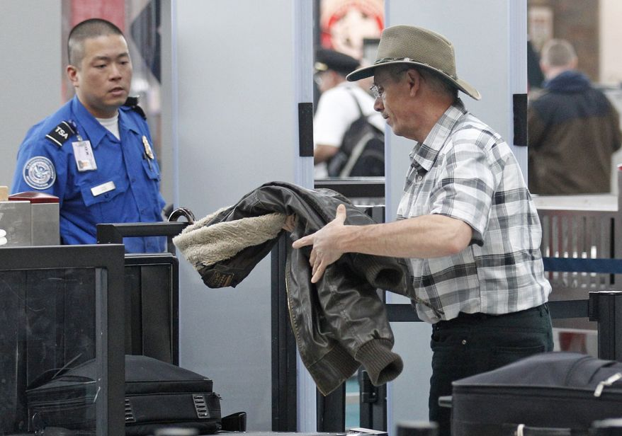 ** FILE ** This April 30, 2012, photo shows a traveler passing through a security check point at Portland International Airport, in Portland, Ore. (AP Photo/Rick Bowmer)