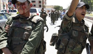 An injured Syrian army soldier (left) walks next to his comrade May 9, 2012, after a roadside bomb hit their military truck in Daraa city, southern Syria. (Associated Press)