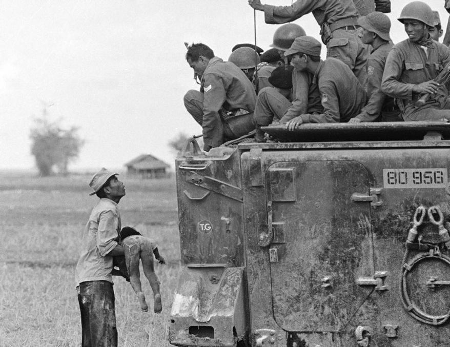 In this March 19, 1964 file photo, one of several shot by Associated Press photographer Horst Faas which earned him the first of two Pulitzer Prizes, a father holds the body of his child as South Vietnamese Army Rangers look down from their armored vehicle. The child was killed as government forces pursued guerrillas into a village near the Cambodian border.  (AP Photo/Horst Faas)