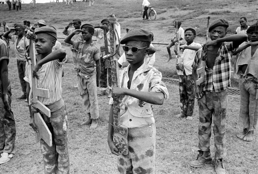 In this Nov. 28, 1961 file photo taken by Associated Press photographer Horst Faas, boys belonging to the Katangese Youth Movement, wearing improvised uniforms of their own design, drill with homemade wooden rifles in the native quarter of Elisabethville, Congo.  (AP Photo/Horst Faas, File)