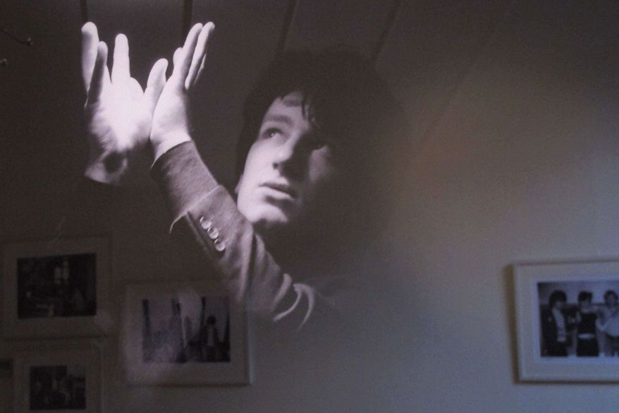 """With other photos reflected behind, a February 1979 photo of an 18-year-old Bono posing under a fluorescent light is one of the more striking images from the """"U2 1978-1981'"""" exhibition opening in Dublin, Ireland, on Thursday, May 10, 2012. (AP Photo/Shawn Pogatchnik)"""