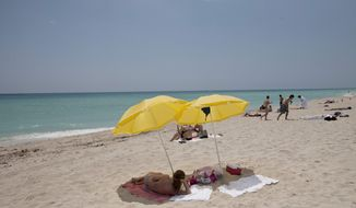 In this Wednesday, May 9, 2012, photo, a sun bather lies under umbrellas on Miami Beach, Fla. In a study released Thursday, May 10, 2012, the Centers for Disease Control and Prevention says half of adults under 30 say they've had a sunburn at least once in the past year. (AP Photo/J. Pat Carter)