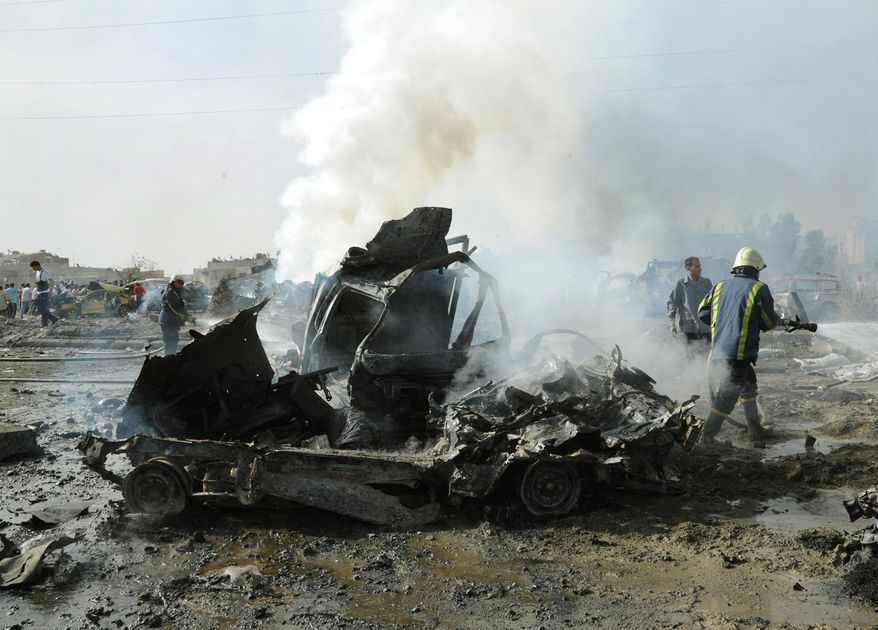 In this photo released by the Syrian official news agency SANA, Syrian fire fighter extinguishes burned cars after two bombs exploded, at Qazaz neighborhood in Damascus, Syria, on Thursday, May 10, 2012. (AP Photo/SANA)