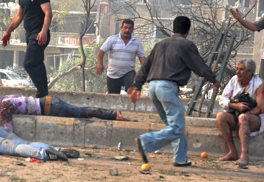 In this photo released by the Syrian official news agency SANA, men run between dead and injured people May 10, 2012, at the scene where two bombs exploded in the Qazaz neighborhood in Damascus, Syria. The large explosions ripped through the Syrian capital, heavily damaging a military intelligence building and leaving blood and human remains in the streets. (Associated Press/SANA)