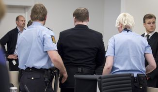 "The self-styled anti-Muslim militant Anders Behring Breivik (center) is escorted May 11, 2012, from a courtroom in Oslo by police after his trial was interrupted briefly by the brother one of his 77 victims. The brother hurled a shoe at him and yelled, ""Go to hell"" before being escorted from the courtroom, police and witnesses said. (Associated Press/NTB scanpix)"