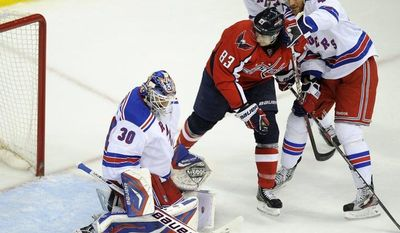 New York Rangers goalie Henrik Lundqvist and Stu Bickel battle for the puck against Washington Capitals center Jay Beagle during Game 4 of their second-round playoff series Saturday, May 5, 2012, in Washington. (AP Photo/Nick Wass)