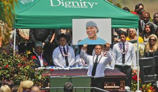 Pastor Miles McPherson of the Rock Church, a former NFL football player, holds up a photo of Junior Seau as Seau's casket rests behind McPherson at Seau's burial on Friday, May 11, 2012, in Oceanside. Seau committed suicide the week prior. (Associated Press)