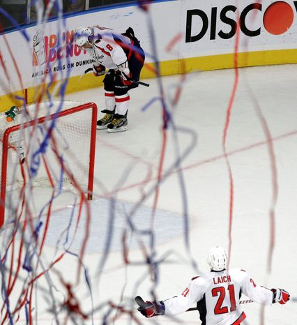 Captain Alex Ovechkin contemplates the Capitals' second-round defeat while Brooks Laich looks on as streamers fall from the rafters at Madison Square Garden on