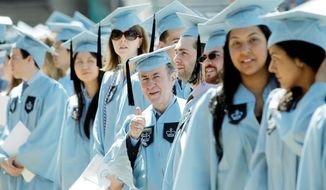 Columbia University janitor Gac Filipaj, an ethnic Albanian who left his native Montenegro 20 years ago to escape war, give a thumbs-up during the School of General Studies graduation ceremony in New York on Sunday. (Associated Press)