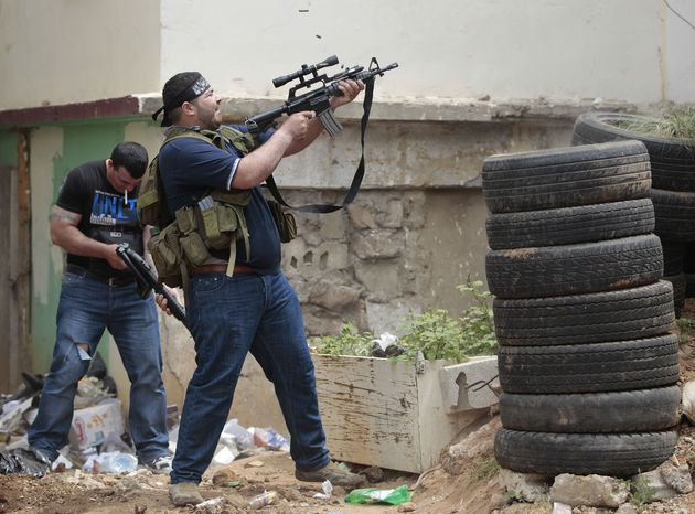 A Sunni gunman fires during clashes in the northern port city of Tripoli, Lebanon, on Sunday, May 13, 2012. (AP Photo/Hussein Malla)