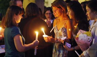 Boston University students, including Tori Pinheiro (third from right) of New Bedford, Mass., hold a candlelight vigil on the university's Marsh Plaza on Saturday, May 12, 2012, in Boston, for three students studying in New Zealand who were killed when their minivan crashed during a weekend trip. Miss Pinheiro was the girlfriend of  Austin Brashears, one of the students who died. (AP Photo/Bizuayehu Tesfaye)