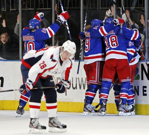 New York Rangers right wing Marian Gaborik (10), center Brad Richards (19), Marc Staal (18) and left wing Carl Hagelin (62), celebrate with Michael Del Zotto, obscured, as Washington Capitals left wing Alexander Semin reacts after Del Zotto scored in the third period of Game 7 of their second-round NHL Stanley Cup playof