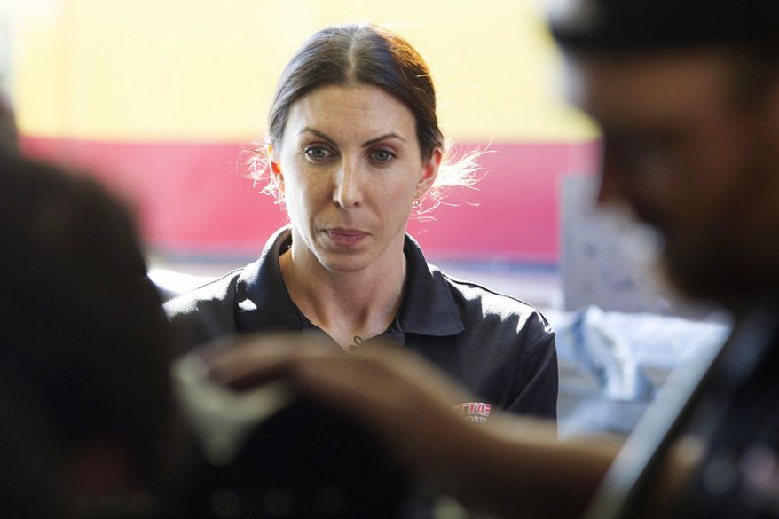 Alexis DeJoria watches as her crew works on her race car in Jupiter, Fla. on Jan, 20, 2012. She is a tattooed mom, an heiress to a billion-dollar empire, and she has been drag racing competitively since 2005. DeJoria, 34, is a ranked National Hot Rod Association driver and the second woman to win a National event in funny car. (AP Photo/J Pat Carter)