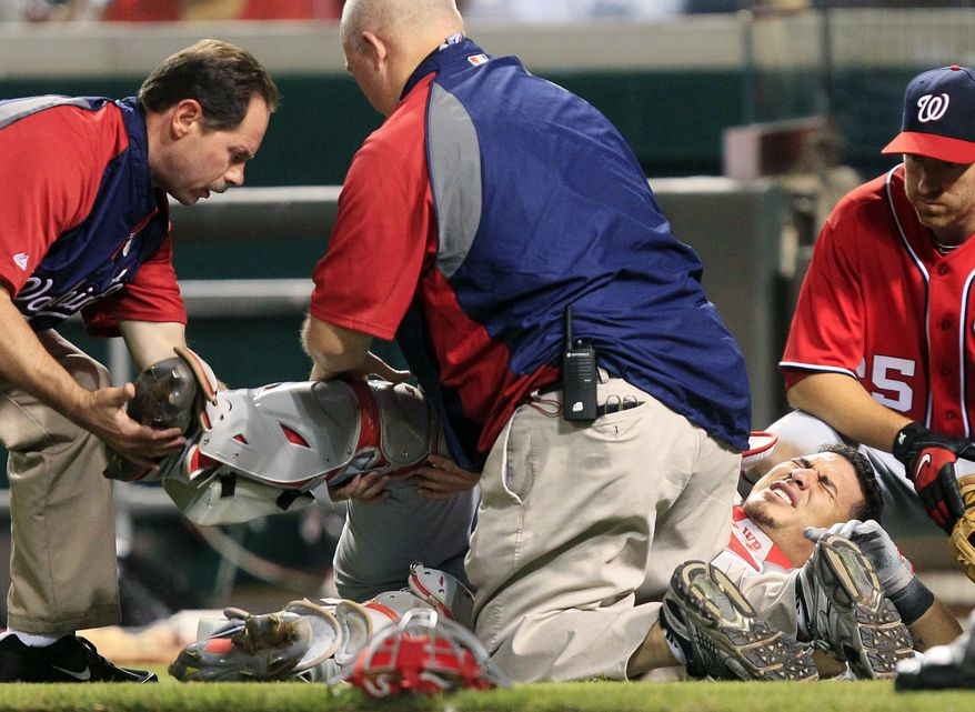 Washington Nationals catcher Wilson Ramos grimaces on the ground after he was injured in the seventh inning against the Cincinnati Reds on Saturday, May 12, 2012, in Cincinnati. Ramos left the game. Washington won 2-1. (AP Photo/Al Behrman)