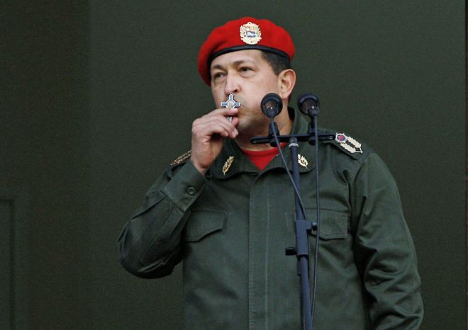 FILE - In this July 4, 2011 file photo, Venezuela's President Hugo Chavez kisses a crucifix as he greets supporters from a balcony in Miraflores presidential palace, after returning from Cuba where he underwent cancer surgery, in Caracas, Venezuela. Chavez has spent much of his career praising the socialist ideas of famed atheists such as Karl Marx and Fidel Castro. However, now in the thick of a prolonged battle against cancer, Chavez is drawing inspiration more than ever from Jesus Christ. (AP Photo/Ariana Cubillos, File)