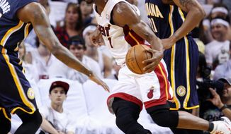 Miami Heat forward Chris Bosh, center, drives past Indiana Pacers guard Paul George, left, and forward David West during the first half of Game 1 in an NBA basketball Eastern Conference semifinal playoff series, Sunday, April 13, 2012, in Miami. Bosh was ruled out of the second half of the game because of what the team called a lower abdominal injury. The Heat won 95-86. (AP Photo/Wilfredo Lee)