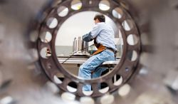 A worker at the Manoir Aerospace plant in Chihuahua City, Mexico, is seen through a part similar to the machined tube he's finishing for a Boeing 777's braking system. Mexico's aerospace industry has taken off. (Keith Dannemiller/Special to The Washington Times)