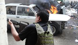 A Sunni gunman fires in a front of burned car on Sunday, May 13, 2012, during a clash in Tripoli, Lebanon. (AP Photo)