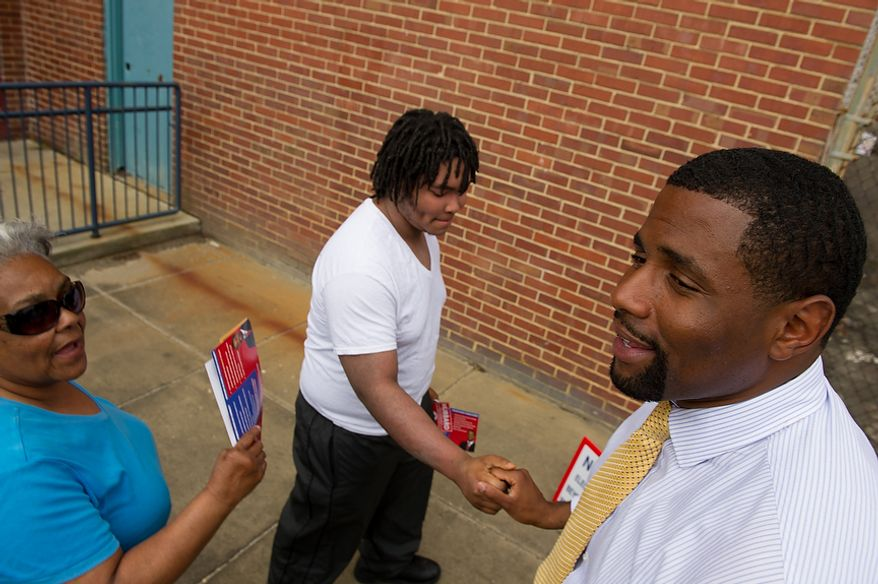 Delano Hunter, right, a candidate running in a special election to replace Harry Thomas for Ward 5 city councilmember, discusses local issues with Bertha Paige, left, and her grandson Aaron Paige, 19, center, as they head to the polls at a University of the District of Columbia Community College building, formerly Backus Middle School, on South Dakota Avenue in Northeast, Washington, D.C., Tuesday, May 15, 2012 (Andrew Harnik/The Washington Times)