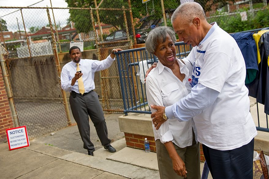 Candidate Delano Hunter, left, watches as candidate Frank Wilds, right, hugs D.C. resident Jean Johnson, outside a University of the District of Columbia Community College building, formerly Backus Middle School, on South Dakota Avenue in Northeast, Washington, D.C., Tuesday, May 15, 2012. Hunter and Wilds are two of the candidates running to replace Harry Thomas for Ward 5 city councilmember in a special election. (Andrew Harnik/The Washington Times)