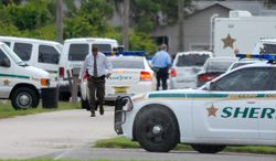 Emergency personnel surround the scene of a multiple shooting in Port St. John in Brevard County, Fla., on Tuesday, May 15, 2012. (AP Photo/Florida Today, Tim Shortt)