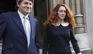 ** FILE ** This Friday, May 11, 2012, file photo shows Rebekah Brooks, former chief executive of News International and her husband Charlie Brooks leaving the High Court in London. Brooks said Tuesday, May 15, 2012, she and her husband will face charges over Britain's tabloid phone hacking scandal. (AP Photo/Sang Tan)