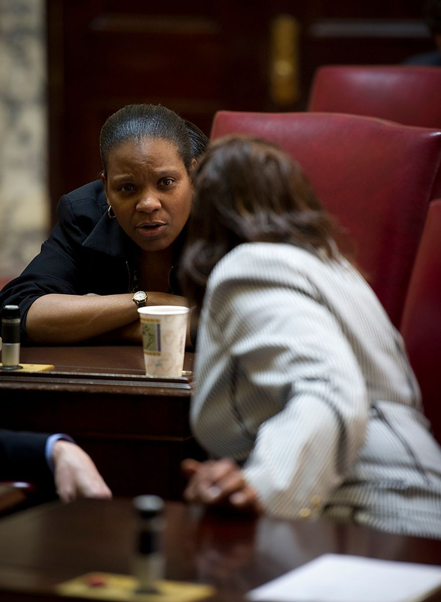 Maryland State Senators Lisa A. Gladden (D-District 41, left) and Joan Carter Conway (D-District 43) confer during the second day of the General Assembly special session at the Maryland State House in Annapolis, Md., Tuesday, May 15, 2012. (Rod Lamkey Jr/The Washington Times)
