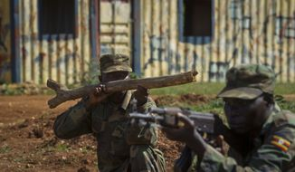 "**FILE** Soldiers from the Uganda People's Defense Force (UPDF), one holding a piece of wood representing a weapon, engage April 30, 2012, in urban operations training in a mock urban setting nicknamed ""Little Mogadishu"" at the Singo training facility in Kakola, Uganda. (Associated Press)"