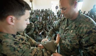 U.S. Marine Sgt. Albert Winschel (right) demonstrates how to apply a tourniquet on fellow Marine Sgt. Preston Norton as they give medic training to soldiers with the Uganda People's Defense Force at the Singo training facility in Kakola. American military advisers there are drawing on experience from Iraq and Afghanistan. (Associated Press)