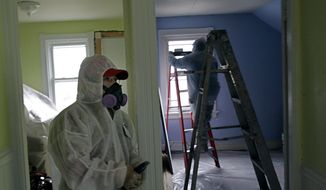Contractors clean up lead paint in a building in Providence, R.I., in 2012. (Associated Press)