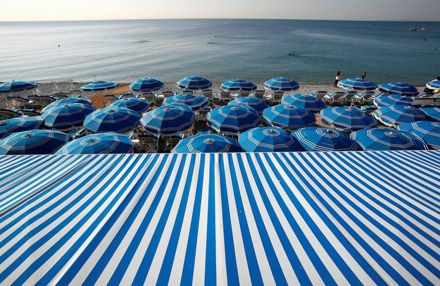 People swim in the Mediterranean Sea as blue beach umbrellas provide shade from the sun along the beach in Nice, southeastern France. (Associated Press)