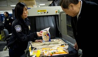 Customs and Border Protection Officer Rebecca Rhinehart asks a passenger about something in his suitcase at Washington Dulles International Airport. Customs officers search for illegal drugs, plants, animal products and food items. (The Washington Times)
